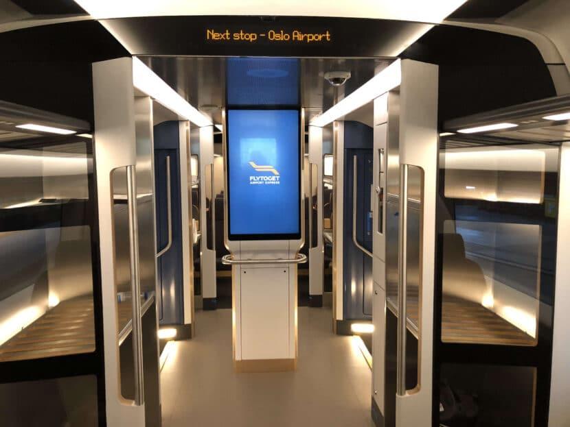 Portaequipajes y pantalla de información al viajero en una plataforma de acceso. FLYTOGET.